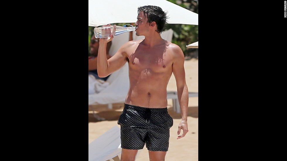 """""""Pretty Little Liars"""" star Tyler Blackburn made sure to stay hydrated while on the beach in Maui in July 2014."""