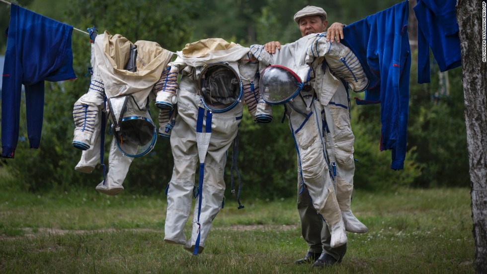 An employee of the Russian Space Training Center hangs spacesuits out to dry after an underwater training exercise Wednesday, July 2, in Moscow. Anatoly Ivanishin of Russia, Kathleen Rubins of the United States and Takuya Onishi of Japan are training for a future mission to the International Space Station.