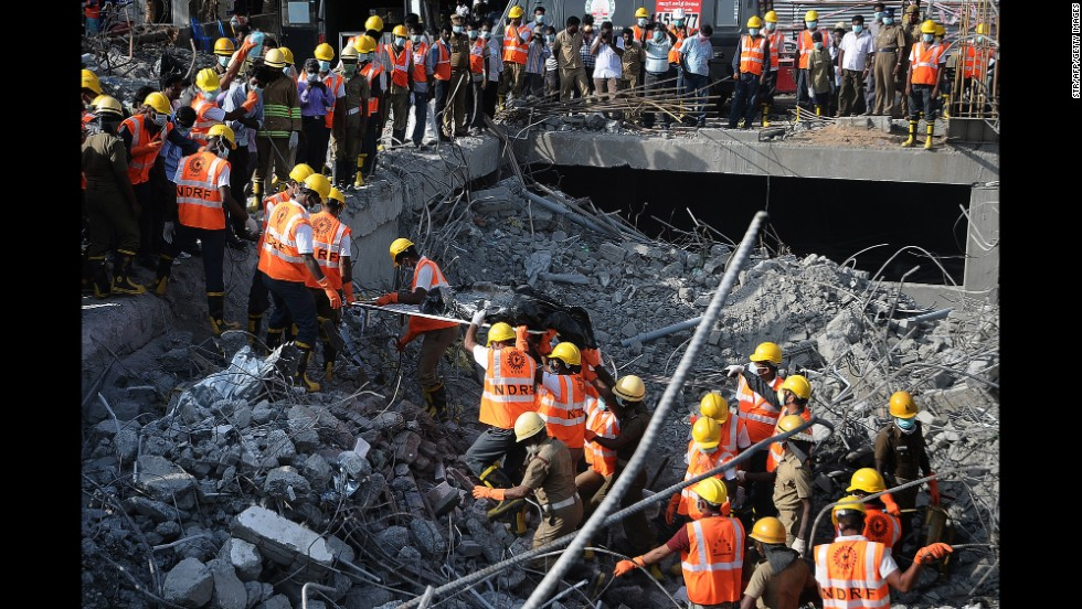 Rescue workers in Chennai, India, carry a victim's body from the rubble of a collapsed building Wednesday, July 2. The 11-story building toppled over during heavy rains June 28, killing dozens of people.