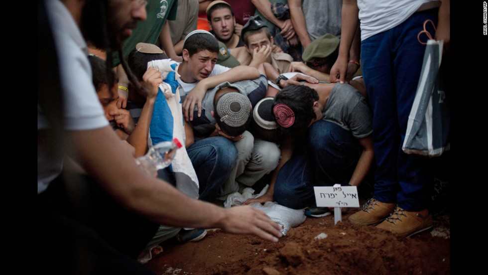Family and friends of Eyal Yifrach, Naftali Frankel and Gilad Shaar mourn over Yifrach's grave during a funeral service Tuesday, July 1, in Modi'in, Israel. The bodies of the three Israeli teenagers were found a day earlier after they were abducted last month on their way home from school in the West Bank.