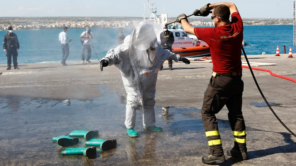 A firefighter cleans a colleague who had just disembarked from a migrant boat that the Italian Navy rescued and towed into the harbor of Pozzallo on Tuesday, July 1. About 30 dead bodies were found on the boat, which Italian media reported had 600 people onboard.