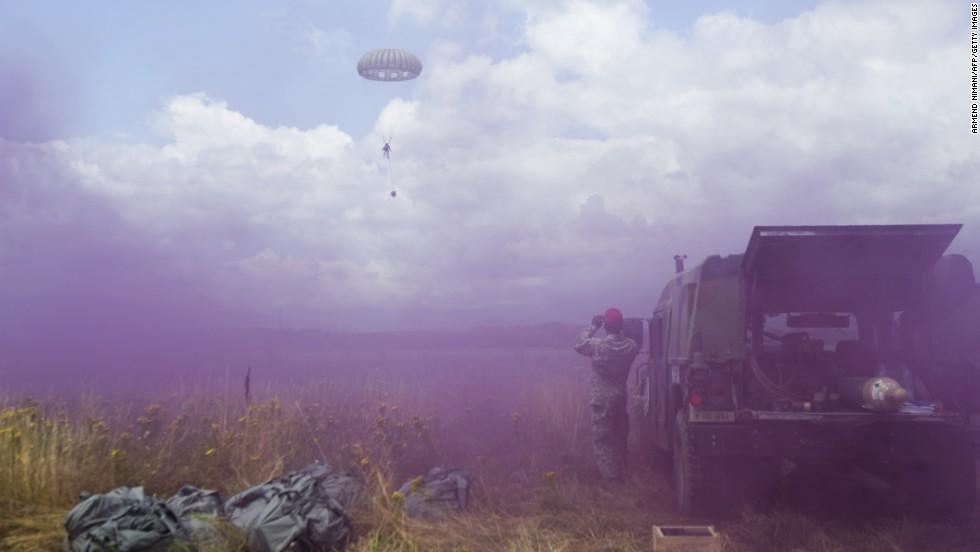 A U.S. Army soldier parachutes to the ground as others throw smoke grenades during a U.S. military exercise near the town of Gjakova, Kosovo, on Tuesday, July 1.