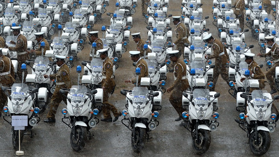 Policemen in Colombo, Sri Lanka, look for shelter Tuesday, July 1, after rain began falling at a ceremony marking the official distribution of new motorcycles to traffic constables across the country.