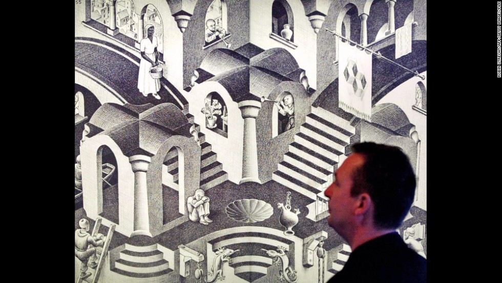 "A man looks at Dutch artist M.C. Escher's artwork ""Hol en Bol"" (1955), displayed at the Escher Museum."