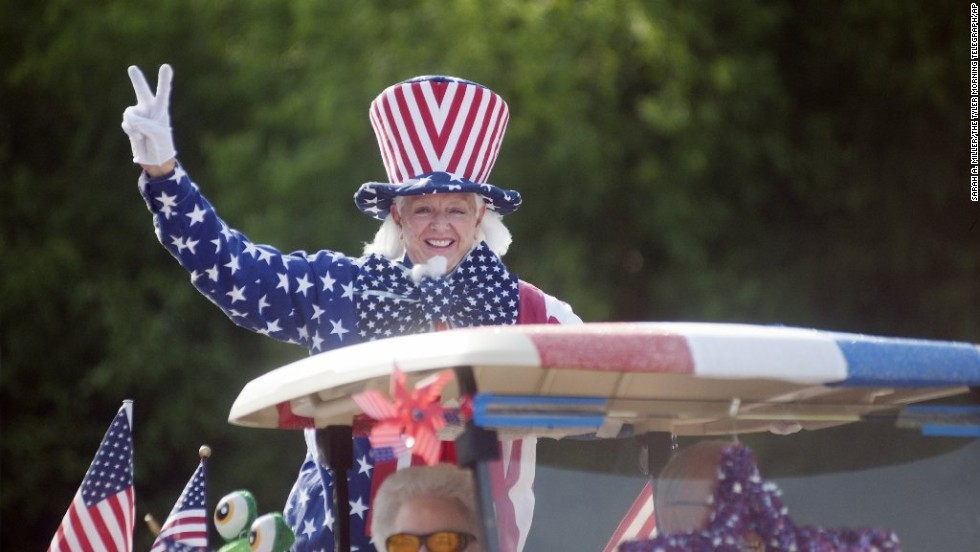 A woman decked out in red, white and blue participates in the annual golf cart parade at the Meadow Lake Senior Living Community in Tyler, Texas.