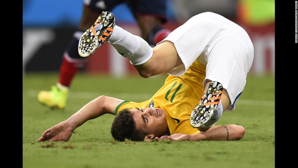 Brazilian midfielder Oscar falls down.
