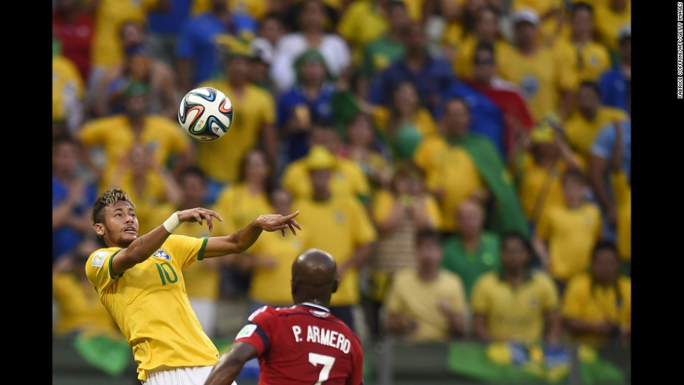 Brazilian forward Neymar heads the ball past Colombian defender Pablo Armero.