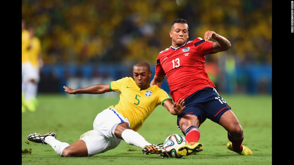 Fernandinho of Brazil, left, tackles Fredy Guarin of Colombia.