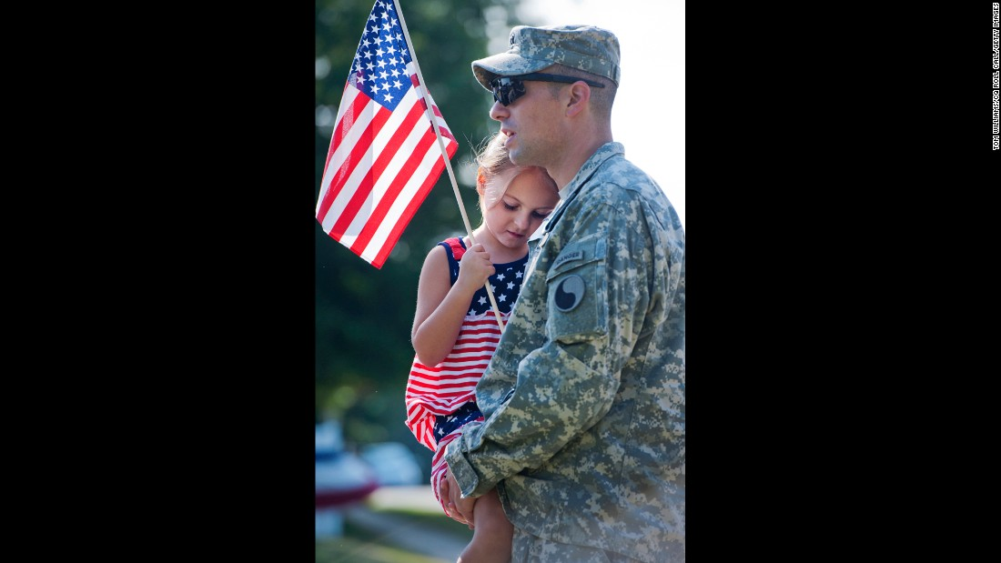 Capt. Brandon Price of the Virginia National Guard and his daughter Chloe prepare to march in a parade in Leesburg, Virginia.