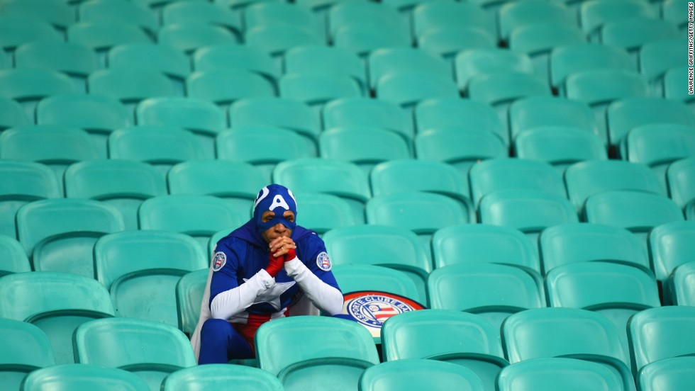 A soccer fan dressed as Captain America sits alone Tuesday, July 1, after the United States lost to Belgium in a World Cup round-of-16 match in Salvador, Brazil.