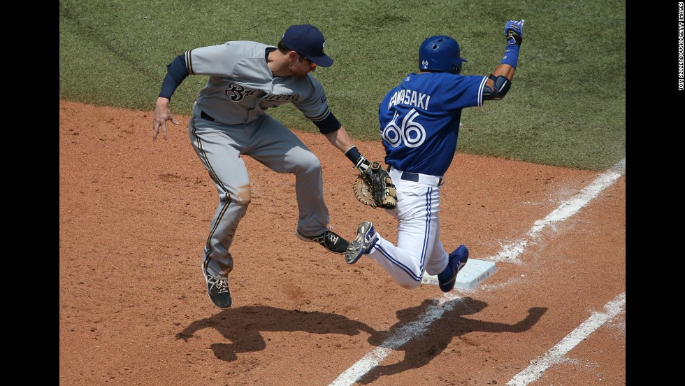 Toronto's Munenori Kawasaki is tagged out at first base by Milwaukee's Jonathan Lucroy during a game in Toronto on Wednesday, July 2.