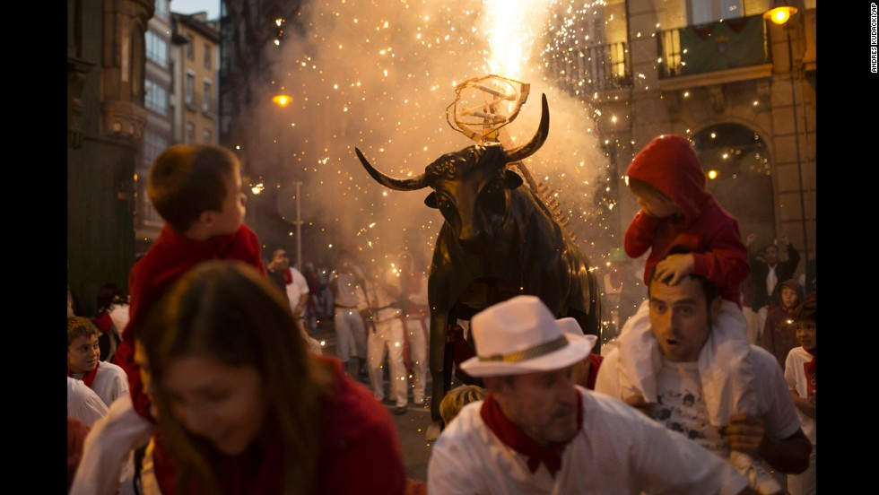 Revelers run away from a flaming fake bull during the second day of the festival on Monday, July 7.