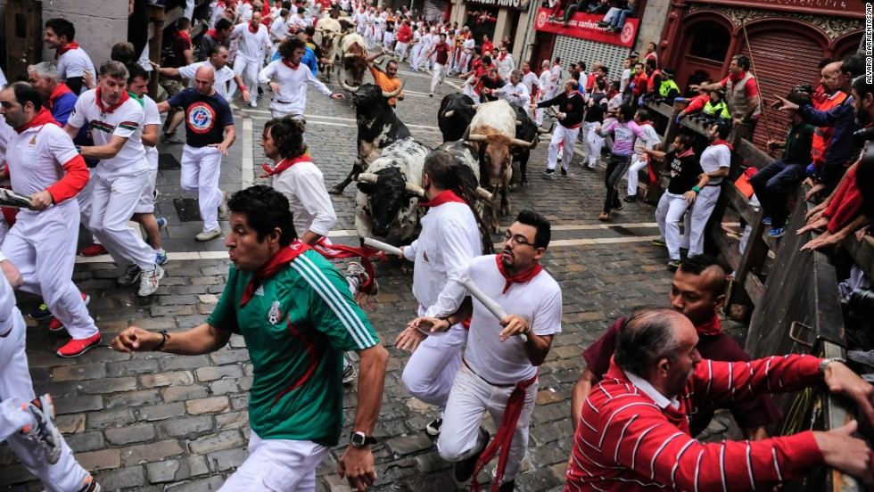 Revelers take part in the bull run on July 7.