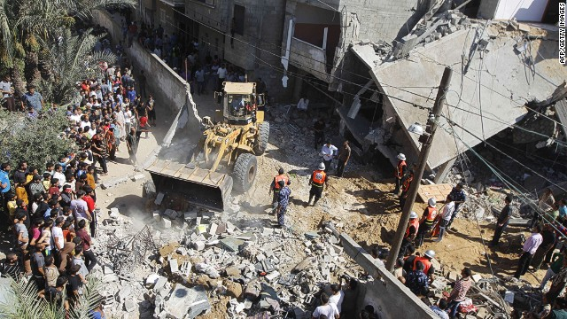 Palestinian rescue workers use a bulldozer to remove debris following an Israeli air strike in Khan Yunis.