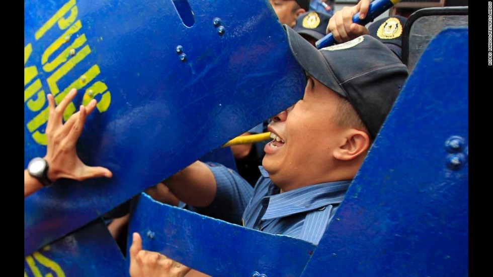 An anti-riot policeman is hit in the face with a colleague's shield after a protester, left, pushed away the shield during a demonstration held Friday, July 4, outside the U.S. Embassy in Manila, Philippines. The protesters commemorated Filipino-American Friendship Day with a rally demanding the pullout of U.S. troops in the Philippines.