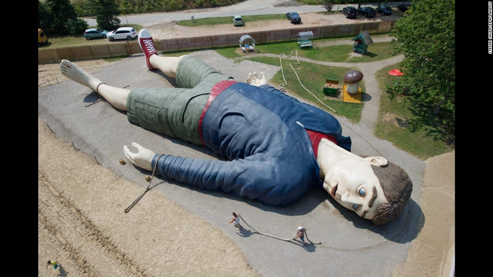 Workers carry a rope next to a sculpture of the literary character Gulliver at the Gulliver's World amusement park in Usedom, Germany, on Tuesday, July 8. The sculpture is 36 meters (118 feet) long.