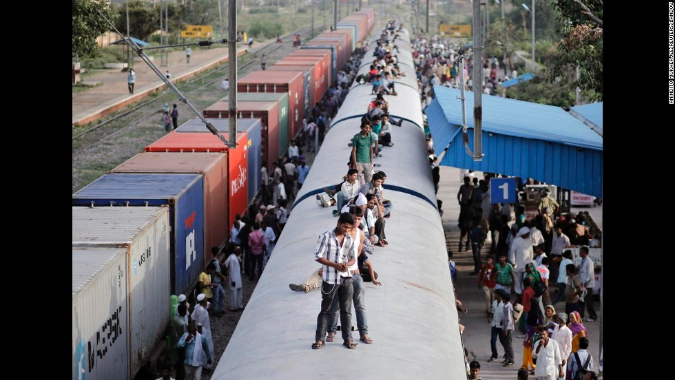 Passengers ride on the top of an overcrowded train in Loni, India, on Monday, July 7.