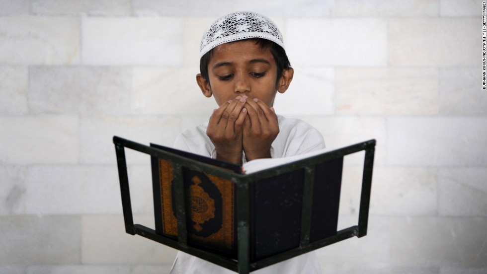 "A Muslim boy recites verses from the Quran at a mosque in Noida, India, on Wednesday, July 9. During <a href=""http://religion.blogs.cnn.com/2014/06/28/the-belief-blog-guide-to-ramadan/"">the holy month of Ramadan</a>, Muslims across the globe are abstaining from food, drink and other pleasures during daylight hours. Many call it a time of spiritual purity and rededication to God."