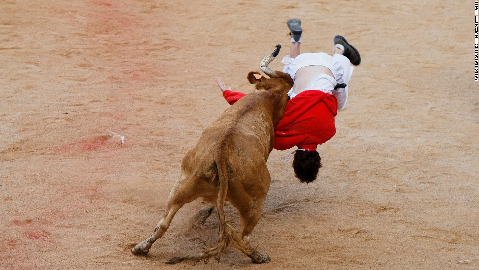 A bull lifts a reveler on July 11.