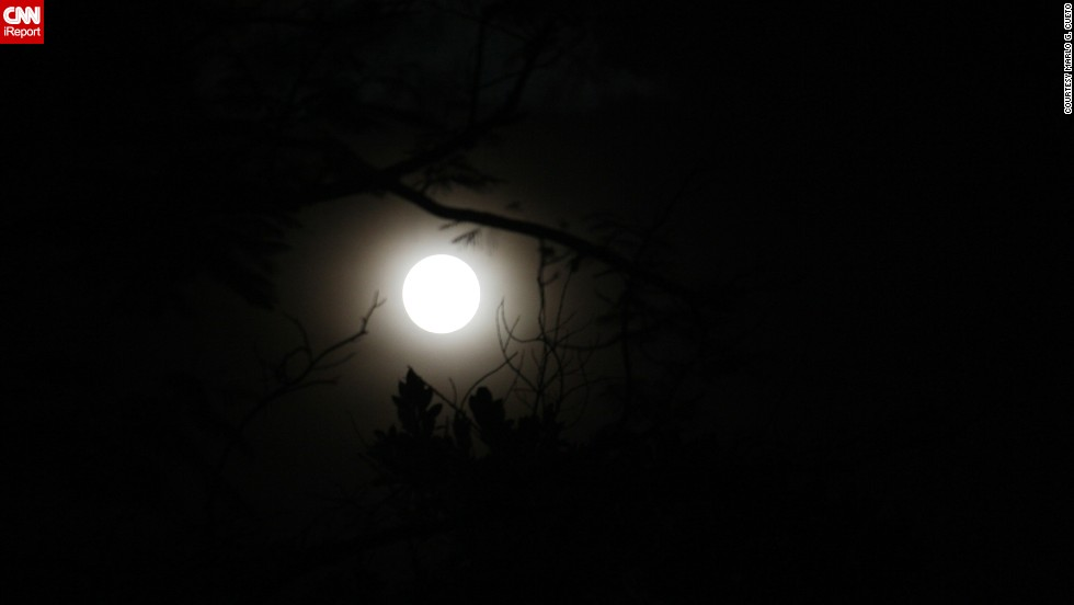 """The supermoon made an exciting appearance in other parts of the world, too. <a href=""""http://ireport.cnn.com/docs/DOC-1152150"""">Marlo Cueto</a> ventured to a park in Makati City, Philippines, so that he could find some sky that wasn't saturated by light pollution. Using a DSLR camera, he photographed the moon through the thick clouds floating above."""
