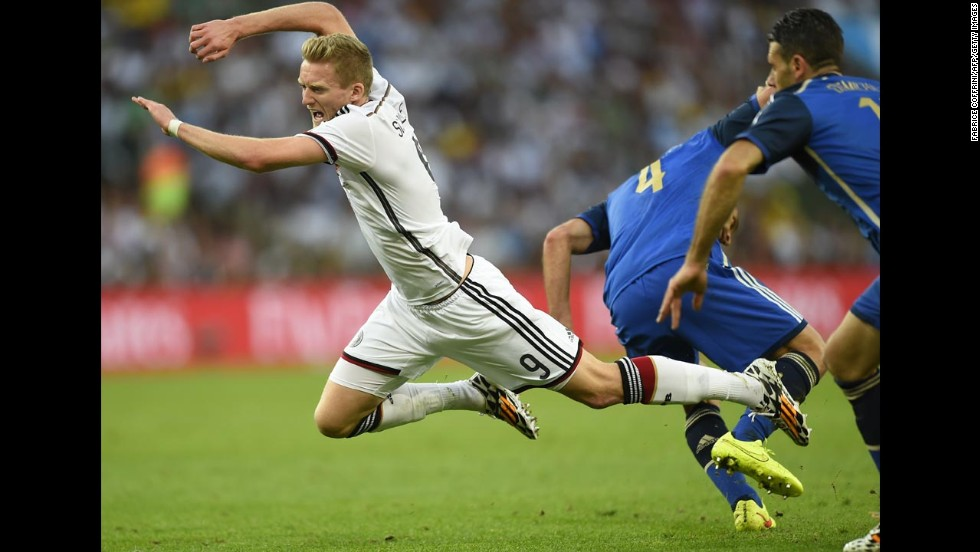 Germany's Andre Schurrle falls to the ground after a challenge from Zabaleta, center.