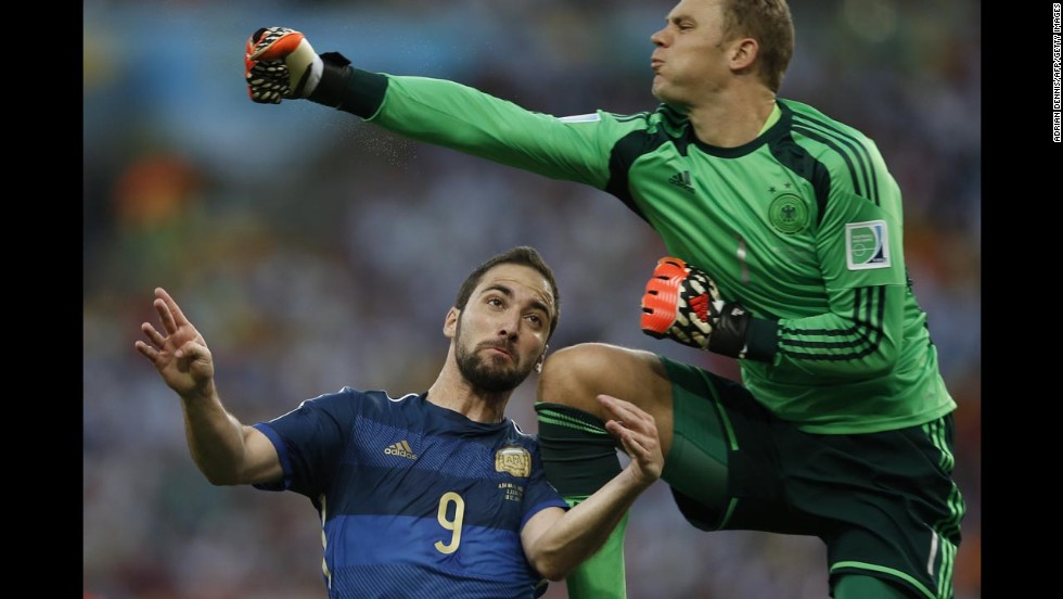 Neuer punches the ball before colliding with Higuain.