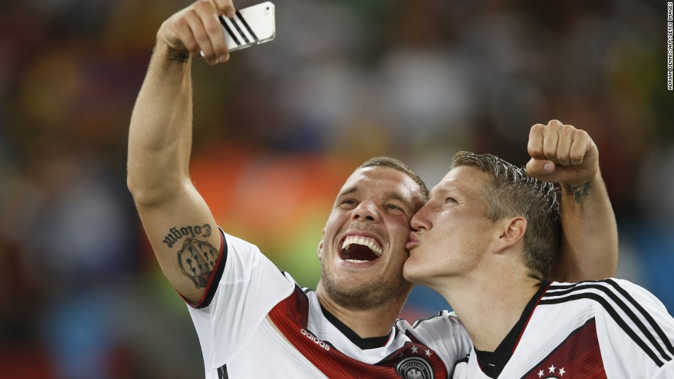 Germany's Lukas Podolski, left, takes a selfie with teammate Bastian Schweinsteiger after the match.