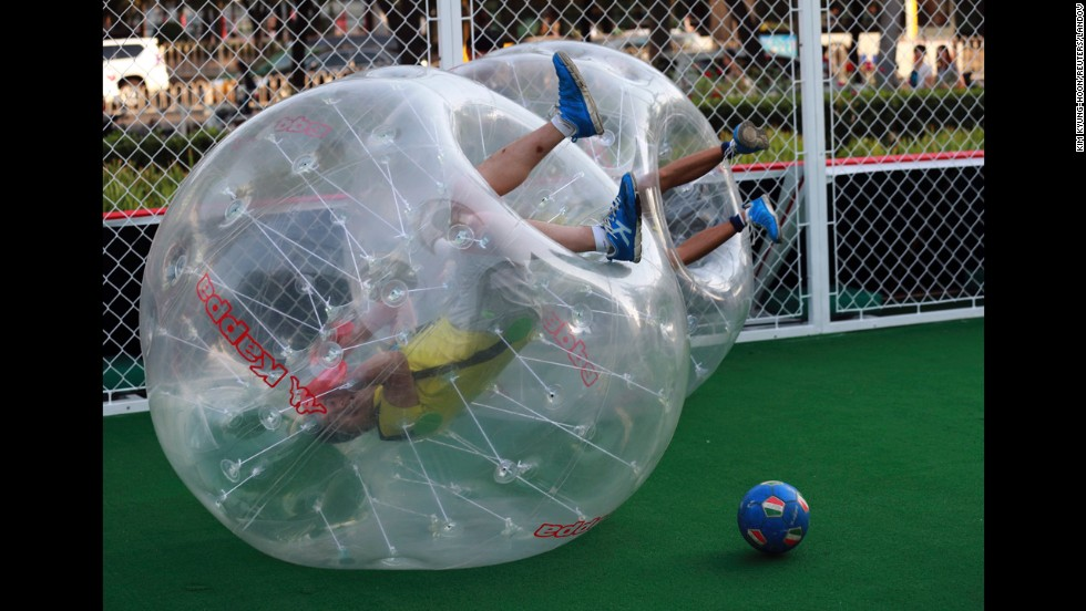 Players partially encased in giant inflatable balls roll over the ground during a bubble soccer match Thursday, July 10, in Beijing. The promotional event was organized by the sportswear company Kappa in conjunction with the World Cup in Brazil.