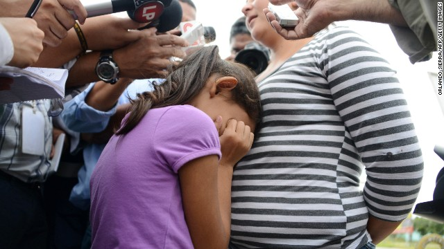 A girl cries as her mother speaks to the press upon arriving in San Pedro Sula, about 260 km north of Tegucigalpa, on July 14, 2014 after being deported from the United States. A first group of 120 deportees from Honduras, El Salvador and Guatemala who had crossed into the United States illegally were repatriated by plane to their countries -- most of the unaccompanied youths. US authorities have detained some 57,000 unaccompanied minors since October, twice the number from the same period a year ago, seeking to illegally cross into the US from Mexico. AFP PHOTO/Orlando SIERRA (Photo credit should read ORLANDO SIERRA/AFP/Getty Images)