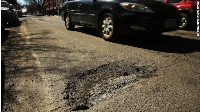 A car travels past a pothole in Brooklyn, New York. After a severe winter, New York City's streets have become treacherous in areas
