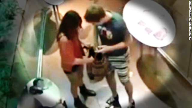 A surveillance image shows a male putting something into a large, multicolored bag carried by a female accomplice.