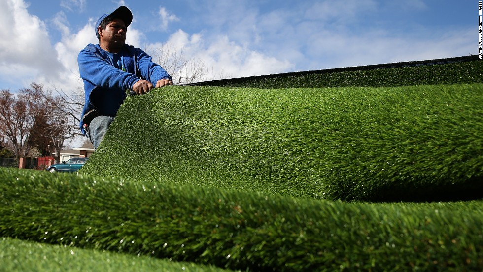 A worker installs an artificial lawn in front of an apartment building in San Jose, California, in January 2014.