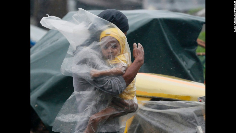 "A Filipino father shelters his child from the strong winds and rain brought by <a href=""http://www.cnn.com/2014/07/15/asia/gallery/typhoon-rammasun/index.html"" target=""_blank"">Typhoon Rammasun</a> in Manila on Wednesday, July 16. The Philippines' first major typhoon of the season has killed more than three dozen people."