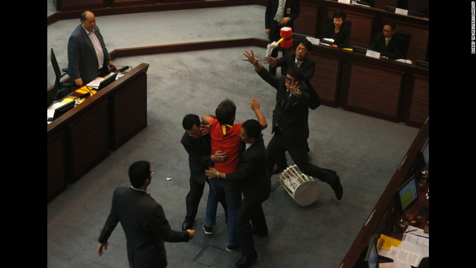 Security guards stop pro-democracy lawmaker Leung Kwok-hung as he throws a plastic hammer toward Hong Kong Chief Secretary Carrie Lam at the Legislative Council in Hong Kong on Tuesday, July 15. Hong Kong's leader formally proposed electoral reforms to Beijing on Tuesday.