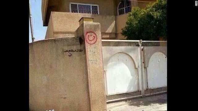 "A house in Mosul, Iraq, has the words ""property of ISIS"" painted on a wall."