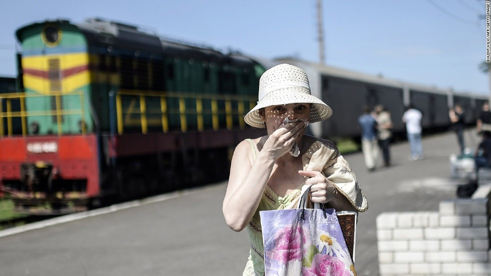 A woman covers her mouth with a piece of fabric July 20, 2014, to ward off smells from railway cars that reportedly contained passengers' bodies.