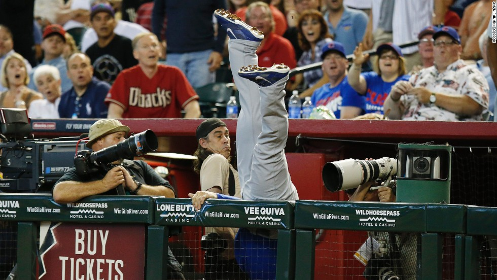 Photographers try to avoid Anthony Rizzo of the Chicago Cubs as he dives to catch a foul ball Sunday, July 20, in Phoenix.