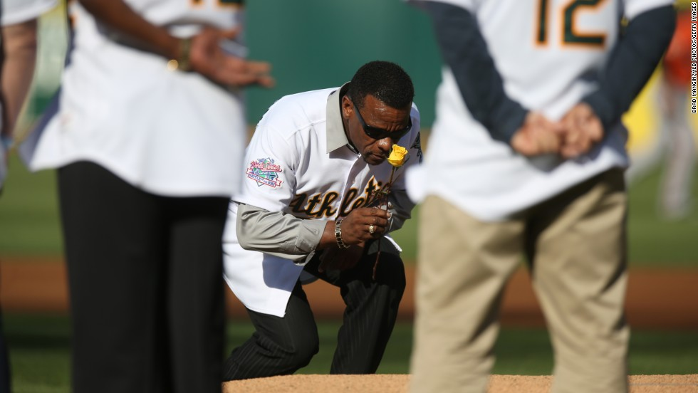 Baseball Hall of Famer Rickey Henderson carries a rose to the pitcher's mound on Saturday, July 19, as he and other members of the 1989 Oakland Athletics team celebrated the 25th anniversary of their World Series win. Henderson laid the rose at the mound in honor of former teammate Bob Welch, who died last month.