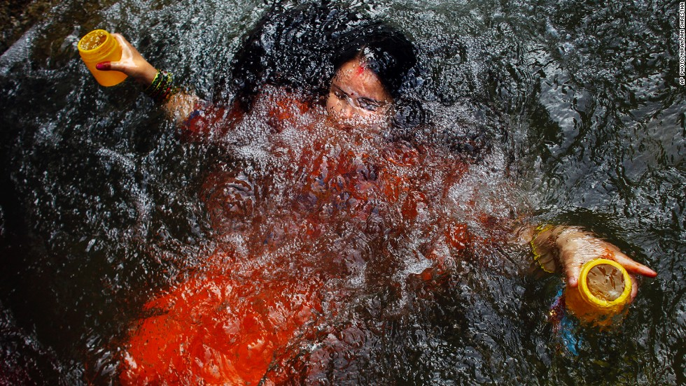 JULY 21 - KATHMANDU, NEPAL: A Hindu devotee takes a dip as she collects holy water from the Bagmati River during the Bol Bom pilgrimage in Sundarijal on the outskirts of Kathmandu. During this event, devotees walk miles barefoot before offering the water at the Pashupatinath temple dedicated to Lord Shiva, the god of destruction.