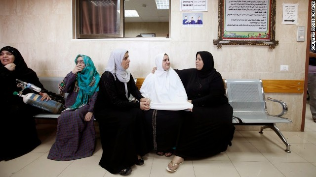 Palestinian women wait to be evacuated from the hospital on Monday.