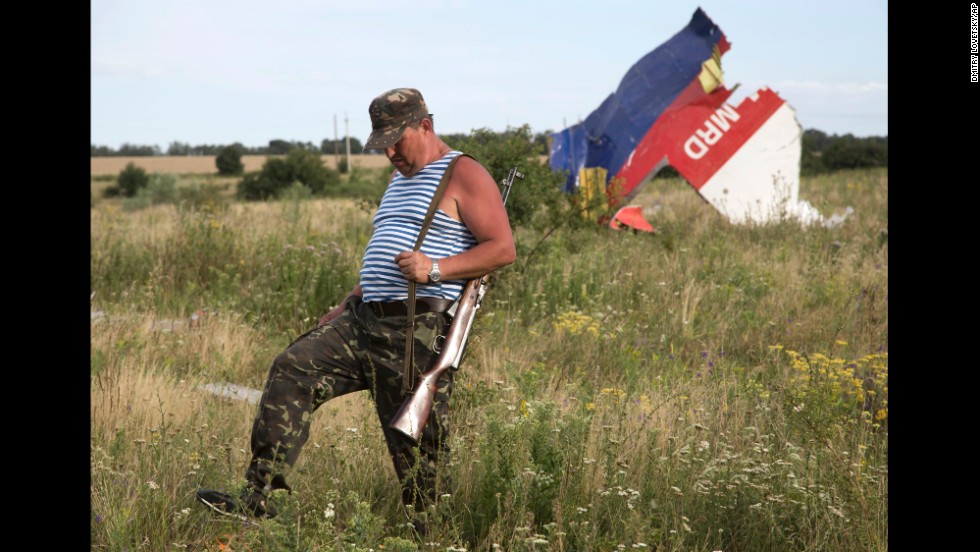 A pro-Russian rebel passes wreckage from the crashed jet near Hrabove on Monday, July 21.