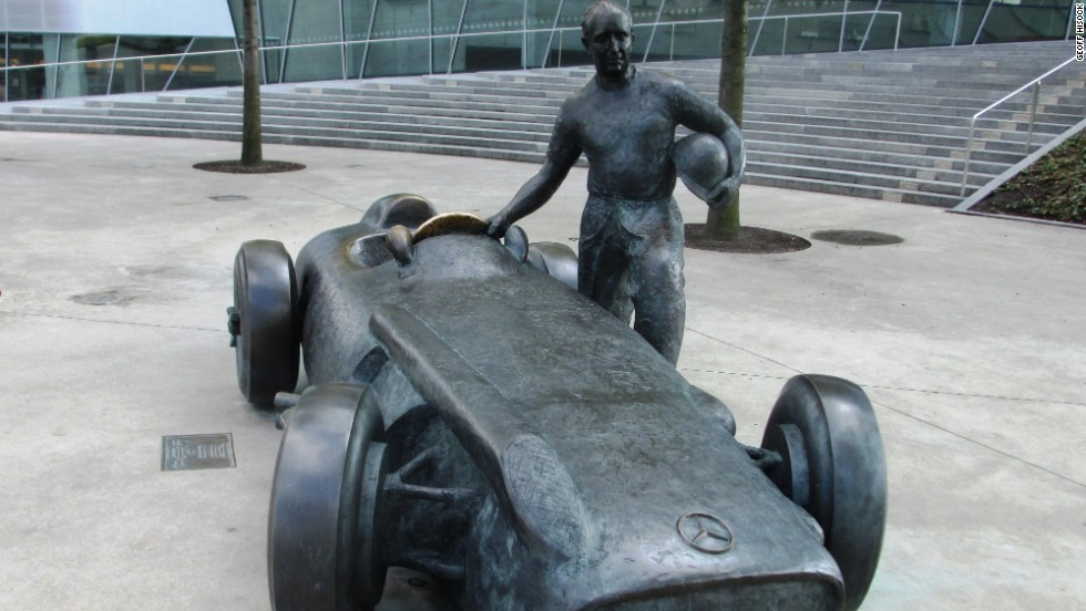 Outside the Mercedes museum, a bronze statue depicts five-time world champion F1 driver Juan Manuel Fangio standing next to his 1954 W196 grand prix racer.