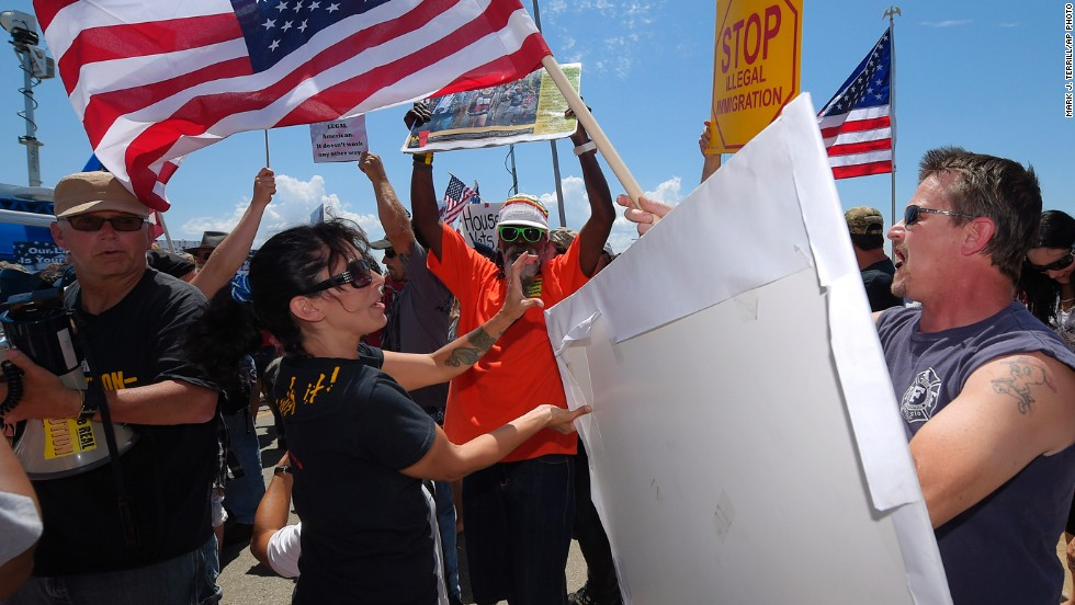 Demonstrators from opposing sides of the immigration issue confront each other outside a U.S. Border Patrol station in Murrieta, California, on Friday, July 4. Some activists are demanding immediate deportation. Others say the migrants are only fleeing violence at home.