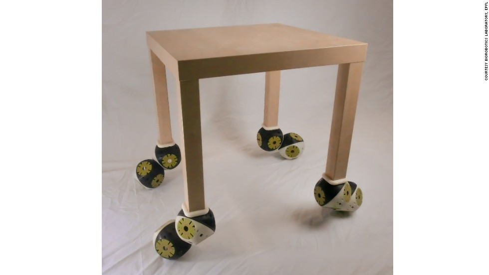 "Roombots modules connected to an existing table, demonstrating its ""plug and play"" capabilities."