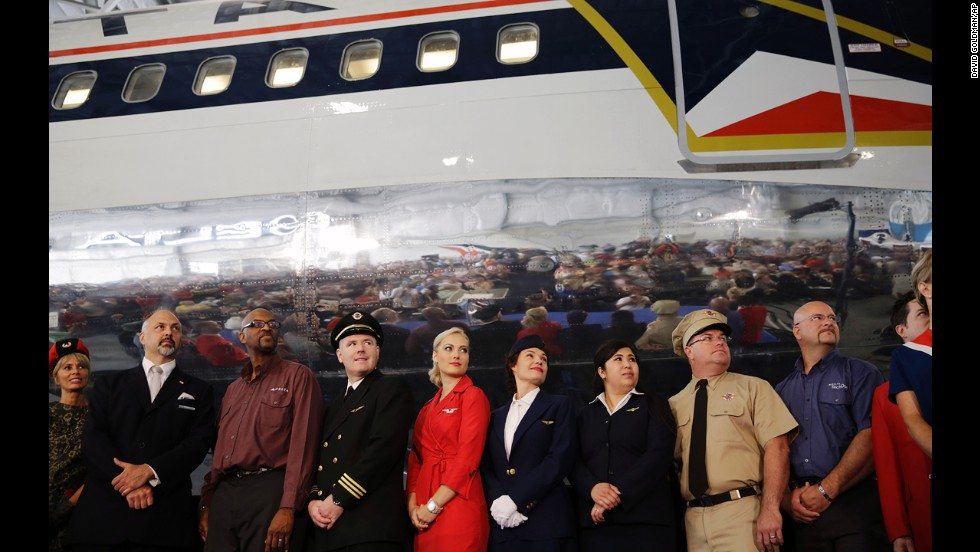 "Airline employees -- some wearing vintage uniforms -- pose in front of a 1980s-era Boeing 767 dubbed ""The Spirit of Delta"" at the museum's June grand opening."