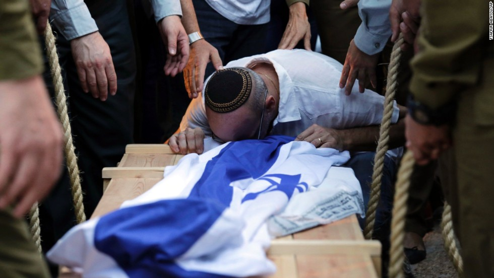 A relative of Israeli soldier Jordan Ben-Simon mourns over his coffin during his funeral in Ashkelon, Israel, on July 22.