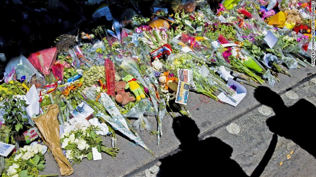 This photo shows the shadows of peopLe looking at flowers placed in remembrance for the victims of the MH17 plane crash at Schiphol Airport, near Amsterdam, on July 23, 2014. The remains of 40 victims from downed Malaysia Airlines flight MH17 headed on July 23 from eastern Ukraine to the Netherlands aboard two planes. Dutch royals were due to meet the planes alongside grieving relatives and representatives from the 11 countries that had citizens among the 298 on board MH17.