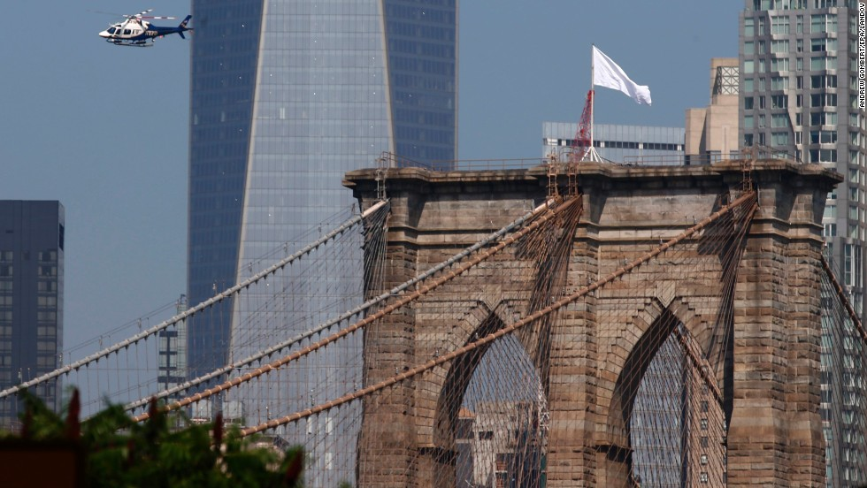 "A New York Police Department helicopter flies over the Brooklyn Bridge on Tuesday, July 22. Police are trying to find out who removed the bridge's two American flags and <a href=""http://www.cnn.com/2014/07/22/us/new-york-brooklyn-bridge-flags/index.html"">replaced them with white flags</a> overnight."