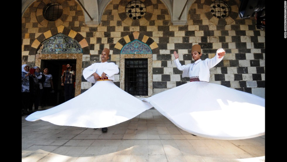 "People watch the <a href=""http://www.cnn.com/2014/07/24/travel/turkey-mevlevi-dervishes/index.html"">""Whirling Dervishes""</a> perform a traditional Sufi dance at a mosque complex in Damascus, Syria, on Monday, July 21. Those in the Order of the Mevlevi, a Sufi sect from the 13th century, are known as ""Whirling Dervishes."" Through the practice of ""sema,"" or listening, in a prayer-induced trance, they aim to act as a bridge between God and humankind."