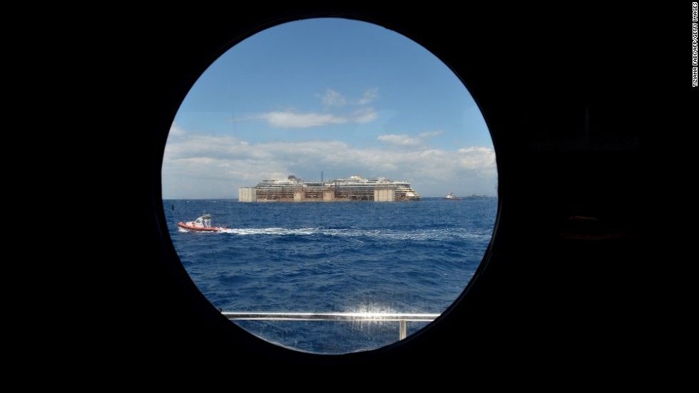 A view from a porthole shows the wreck of the Costa Concordia as it's being towed on July 23. It'll take about two years to dismantle the massive cruise liner.<br />